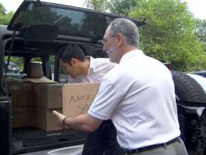 Bob Daria and Manav Lalwani of American Spraytech load products destined for homeless vets.